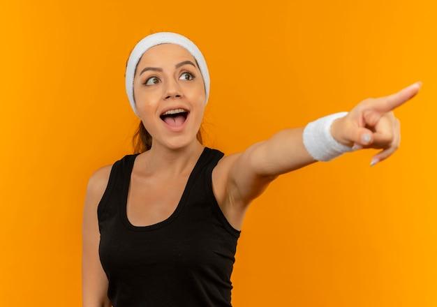 Молодая фитнес-женщина в спортивной одежде с повязкой на голову счастлива и удивлена, указывая пальцем в сторону, стоящую над оранжевой стеной