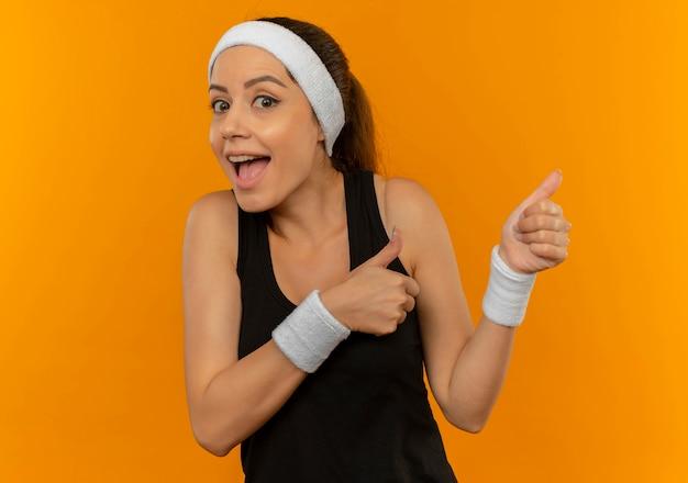 Молодая фитнес-женщина в спортивной одежде с повязкой на голову счастлива и удивлена, указывая пальцами в сторону, стоящую над оранжевой стеной
