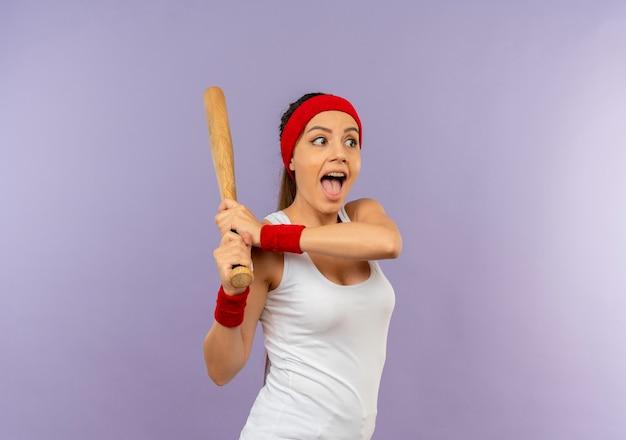 灰色の壁の上に立って幸せで興奮して遊んでいる野球のバットを保持しているヘッドバンドとスポーツウェアの若いフィットネス女性