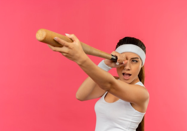 ピンクの壁の上に立っているスパイグラスとして使用して野球のバットを保持しているヘッドバンドとスポーツウェアの若いフィットネス女性