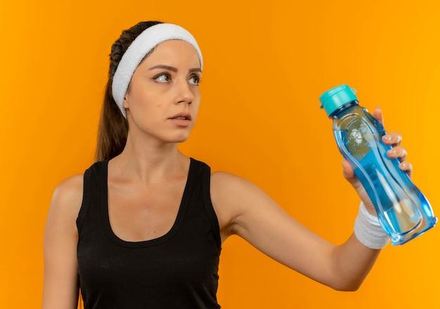オレンジ色の壁の上に立って混乱して脇を見ている水のボトルを保持しているヘッドバンドとスポーツウェアの若いフィットネス女性