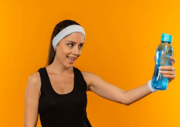 오렌지 벽 위에 서있는 얼굴에 미소로보고 물 한 병을 들고 머리띠와 운동복에 젊은 피트 니스 여자