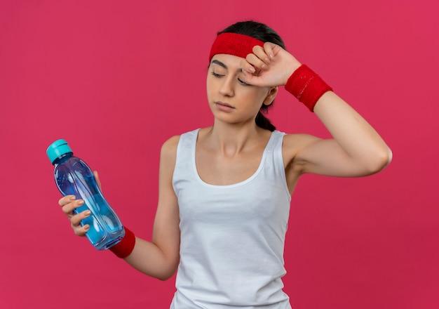 핑크 벽 위에 피곤 서 찾고 물 한 병을 들고 머리띠와 운동복에 젊은 피트 니스 여자
