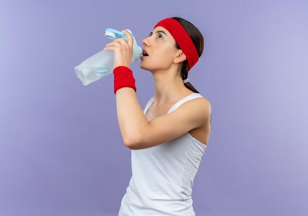 보라색 벽 위에 피곤 서 찾고 물 한 병을 들고 머리띠와 운동복에 젊은 피트 니스 여자