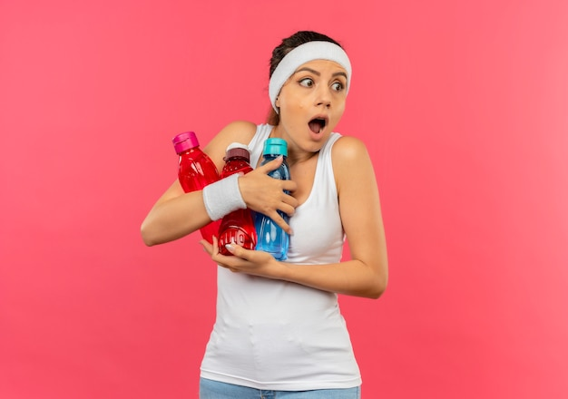 ピンクの壁の上に立って驚いて脇を見ている水のボトルを保持しているヘッドバンドとスポーツウェアの若いフィットネス女性
