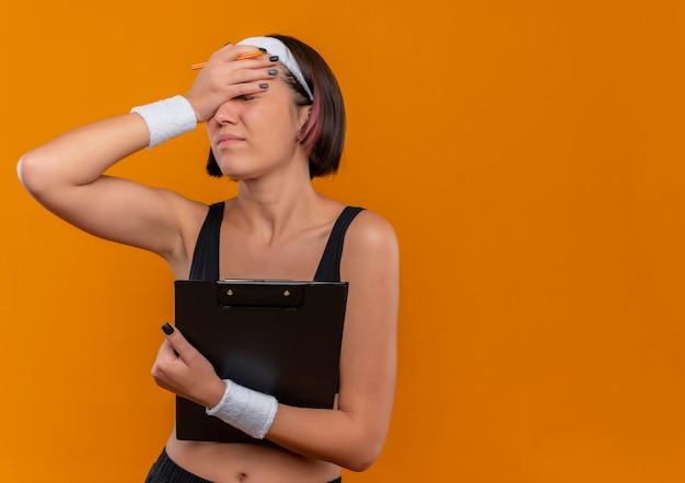 Молодая фитнес-женщина в спортивной одежде с повязкой на голову, держащая буфер обмена, выглядит уставшей и скучающей, прикрывая глаза рукой, стоящей над оранжевой стеной
