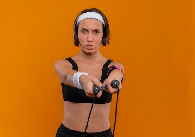 오렌지 벽 위에 서있는 자신감이 식으로 밧줄을 건너 뛰는 머리띠를 들고 운동복에 젊은 피트 니스 여자
