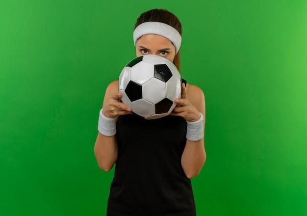 緑の壁の上に立って覗くその後ろに顔を隠してサッカーボールを保持しているヘッドバンドとスポーツウェアの若いフィットネス女性