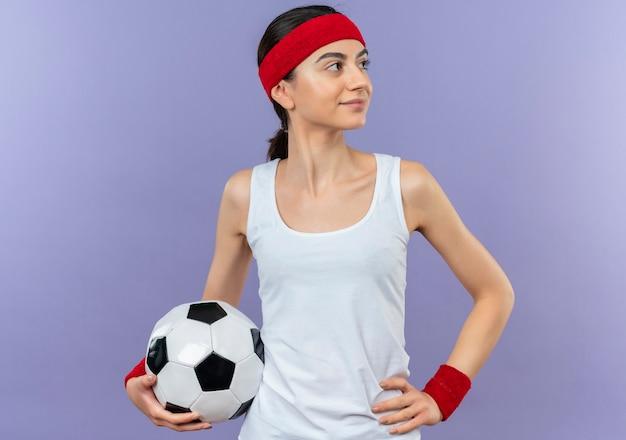 紫色の壁の上に立っている顔に自信を持って笑顔で脇を見てサッカーボールを保持しているヘッドバンドとスポーツウェアの若いフィットネス女性