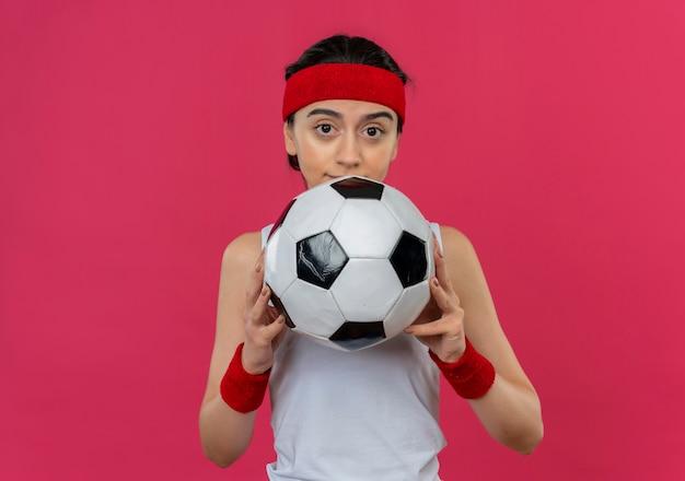 ピンクの壁の上に立っているカメラで混乱しているように見えるサッカーボールを保持しているヘッドバンドとスポーツウェアの若いフィットネス女性