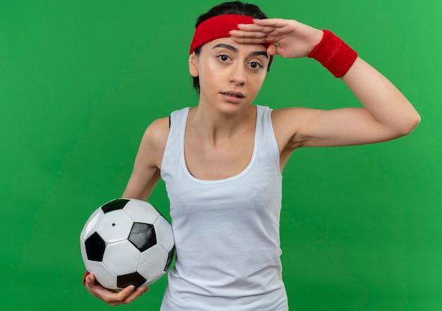 Молодая фитнес-женщина в спортивной одежде с повязкой на голову, держащая футбольный мяч, смотрит вдаль с рукой над головой, стоя над зеленой стеной