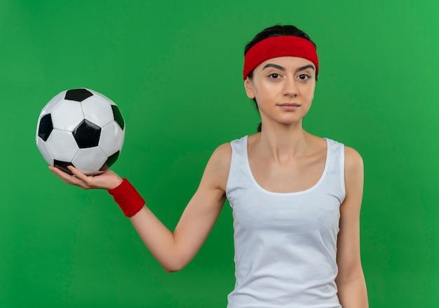 緑の壁の上に立っている自信を持って表情でサッカーボールを保持しているヘッドバンドとスポーツウェアの若いフィットネス女性
