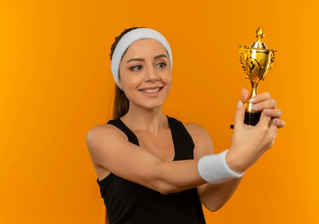 머리띠 트로피를 들고 행복하고 긍정적 인 오렌지 벽 위에 유쾌하게 서 웃고있는 스포츠웨어에 젊은 피트 니스 여자