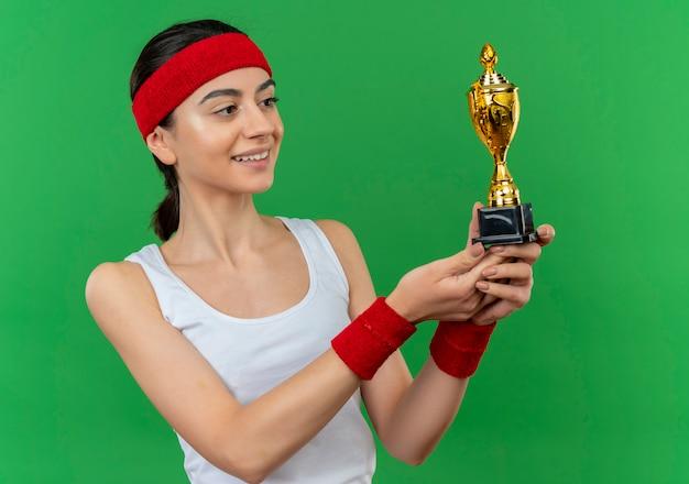 녹색 벽 위에 자신감 서 웃 고 그것을보고 트로피를 들고 머리띠와 스포츠웨어에 젊은 피트 니스 여자