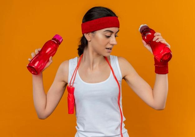 オレンジ色の壁の上に立っている疑いを持って混乱しているように見える2本の水を保持しているヘッドバンドを持つスポーツウェアの若いフィットネス女性