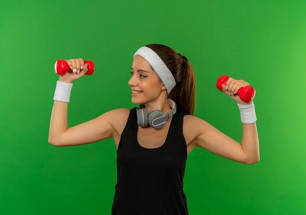 緑の壁の上に立っている顔に笑顔で自信を持って見える運動をしている2つのダンベルを保持しているヘッドバンドを持つスポーツウェアの若いフィットネス女性