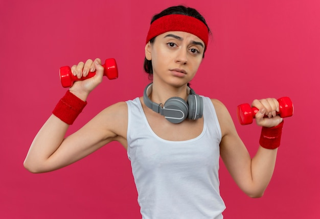 분홍색 벽 위에 서있는 얼굴에 슬픈 표정으로 운동을하는 두 아령을 들고 머리띠와 운동복에 젊은 피트 니스 여자