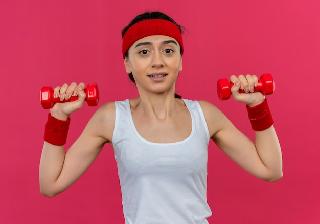 Молодая фитнес-женщина в спортивной одежде с повязкой на голову, держащая две гантели в поднятых руках, смущенная, стоя над розовой стеной