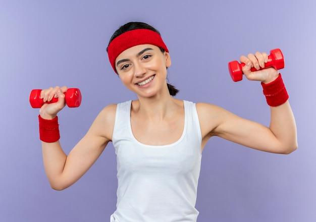 Молодая фитнес-женщина в спортивной одежде с повязкой на голову, держащая две гантели в поднятых руках, весело улыбаясь, делает упражнения, стоя над фиолетовой стеной
