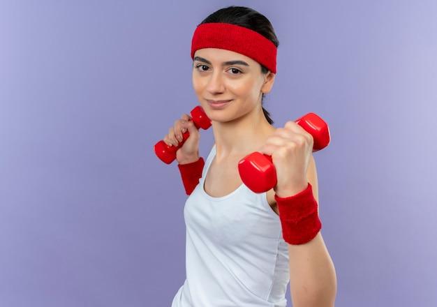 Молодая фитнес-женщина в спортивной одежде с повязкой на голову, держащая две гантели в поднятых руках, уверенно улыбаясь, делает упражнения, стоя над фиолетовой стеной