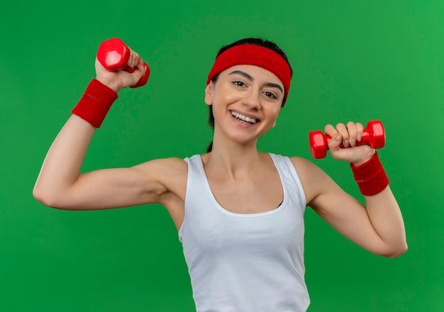Молодая фитнес-женщина в спортивной одежде с повязкой на голову держит две гантели, поднимая руки, делая упражнения, уверенно улыбаясь, стоя над зеленой стеной