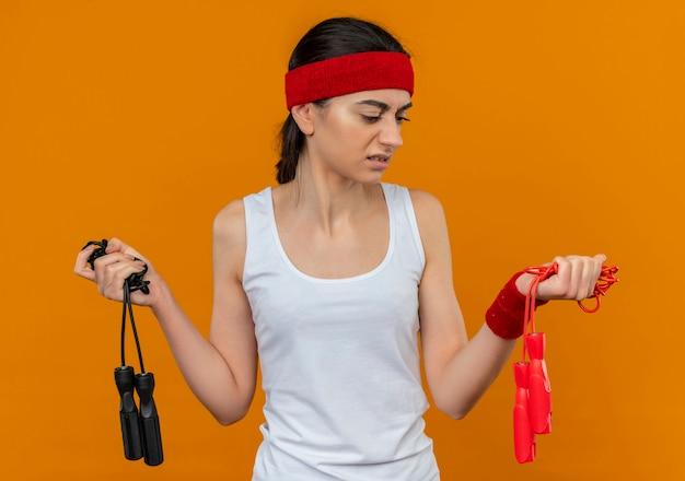 오렌지 벽 위에 서있는 의심을 갖는 혼란스러워 보이는 두 개의 건너 뛰는 밧줄을 들고 머리띠와 운동복에 젊은 피트 니스 여자