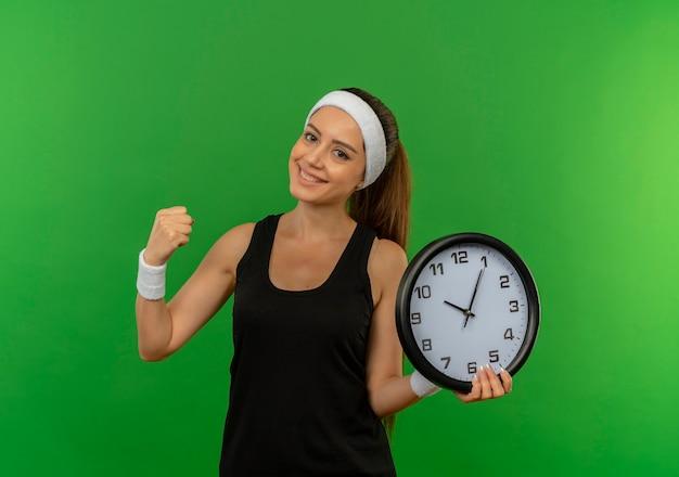 緑の壁の上に立って幸せで前向きな笑顔の拳を握り締める壁時計を保持しているヘッドバンドとスポーツウェアの若いフィットネス女性