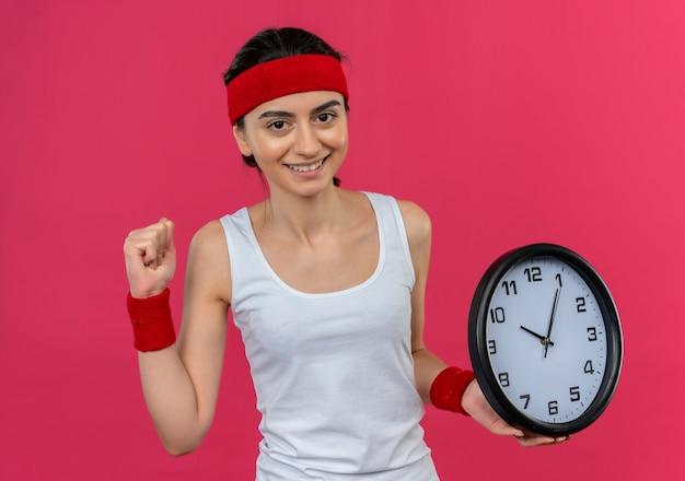 ピンクの壁の上に元気に幸せで前向きに立って笑顔の拳を握り締める壁時計を保持しているヘッドバンドとスポーツウェアの若いフィットネス女性