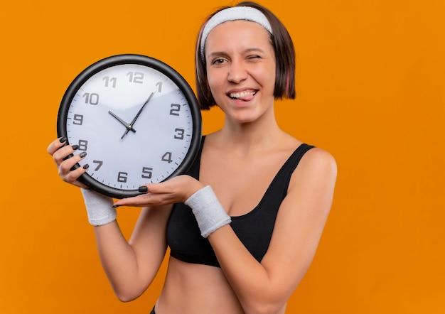 オレンジ色の壁の上に立っている舌を突き出て幸せなポジティブな壁時計を保持しているヘッドバンドとスポーツウェアの若いフィットネス女性