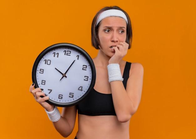 オレンジ色の壁の上に立っているストレスと神経質な噛む爪を脇に見て壁時計を保持しているヘッドバンドを持つスポーツウェアの若いフィットネス女性