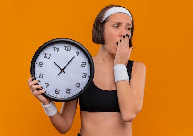 オレンジ色の壁の上に立って疲れて退屈なあくびを探している壁時計を保持しているヘッドバンドとスポーツウェアの若いフィットネス女性