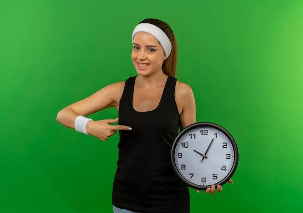 緑の壁の上に立って自信を持って笑ってそれに指で指している壁時計を保持しているヘッドバンドを持つスポーツウェアの若いフィットネス女性