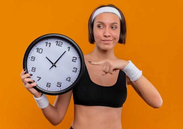 オレンジ色の壁の上に立っている顔に自信を持って笑顔でそれに指で指している壁時計を保持しているヘッドバンドを持つスポーツウェアの若いフィットネス女性