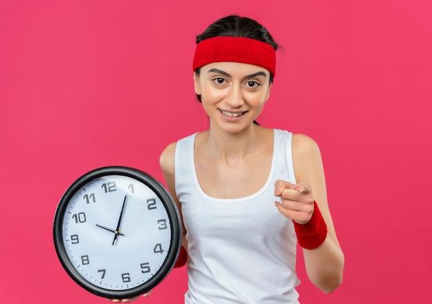 ピンクの壁の上に立っている顔に笑顔でカメラにインデックスで指している壁時計を保持しているヘッドバンドを持つスポーツウェアの若いフィットネス女性