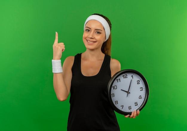 녹색 벽 위에 자신감 서 웃 고 검지 손가락을 보여주는 벽 시계를 들고 머리띠와 스포츠웨어에 젊은 피트 니스 여자