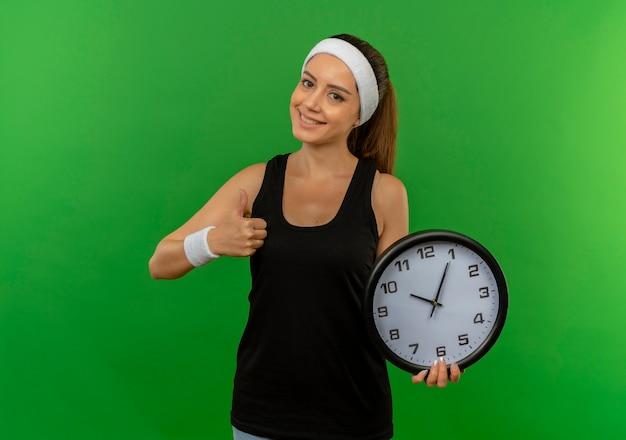 녹색 벽 위에 서 웃 고 엄지 손가락을 보여주는 벽 시계를 들고 머리띠와 스포츠웨어에 젊은 피트 니스 여자