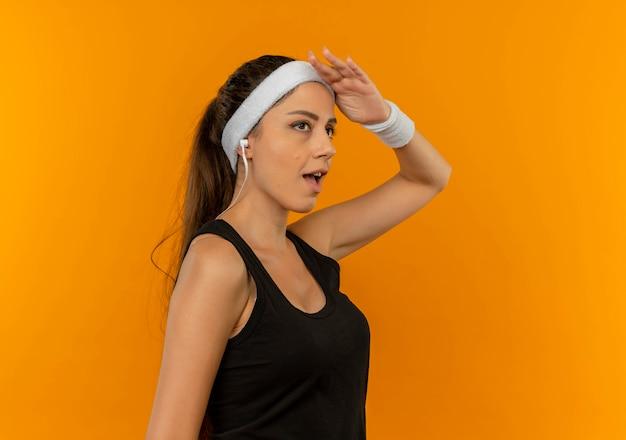 Молодая фитнес-женщина в спортивной одежде с повязкой на голову смотрит в сторону с уверенным выражением лица, отдавая честь стоя над оранжевой стеной
