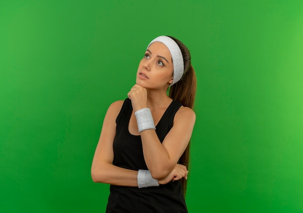 녹색 벽 위에 서있는 잠겨있는 표정으로 턱에 손으로 제쳐두고 찾고 머리띠와 운동복에 젊은 피트 니스 여자
