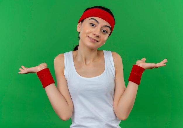 Молодая фитнес-женщина в спортивной одежде с повязкой на голове выглядит смущенной и неуверенно пожимающей плечами, не имея ответа, стоя у зеленой стены
