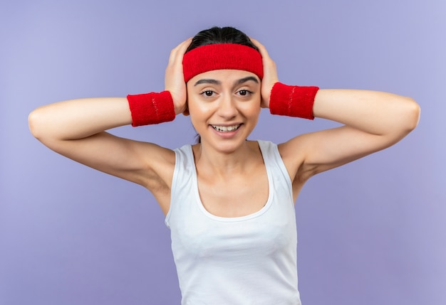 紫色の壁の上に立っている腕で彼女の頭を保持して驚いて驚いたように見えるヘッドバンドを持つスポーツウェアの若いフィットネス女性