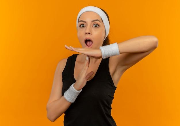 Молодая фитнес-женщина в спортивной одежде с оголовьем выглядит удивленной, делая жест тайм-аута с руками, стоящими над оранжевой стеной