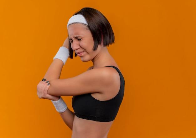 Молодая фитнес-женщина в спортивной одежде с повязкой на голову выглядит нездоровой, касаясь ее локтя, чувствуя боль, стоя над оранжевой стеной