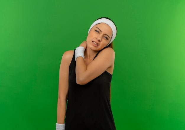 緑の壁の上に立っている痛みを持っている肩に触れて体調不良に見えるヘッドバンドを持つスポーツウェアの若いフィットネス女性