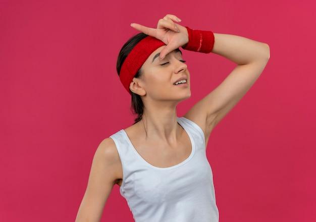 ピンクの壁の上に立っている目を閉じて彼女の頭の上に指で敗者のジェスチャーを作るヘッドバンドとスポーツウェアの若いフィットネス女性
