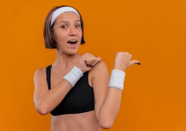 オレンジ色の壁の上に立っている親指で前向きで幸せなヘッドバンドとスポーツウェアの若いフィットネス女性