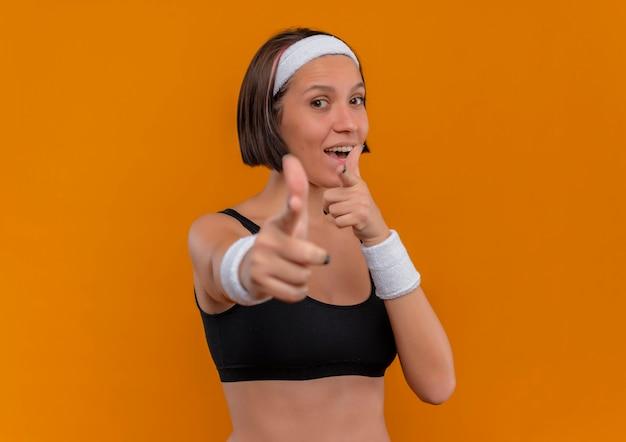 オレンジ色の壁の上に立っているカメラに人差し指でポジティブで幸せなヘッドバンドを指しているスポーツウェアの若いフィットネス女性