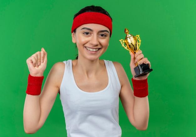 녹색 벽 위에 자신감이 서 웃고 승자처럼 머리띠가 주먹을 올리는 운동복에 젊은 피트 니스 여자