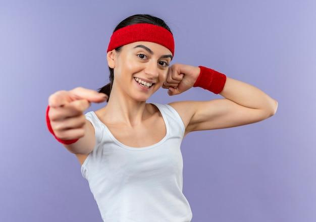 紫色の壁の上に立って自信を持って笑顔のカメラに指を指して拳を上げるヘッドバンドを持つスポーツウェアの若いフィットネス女性