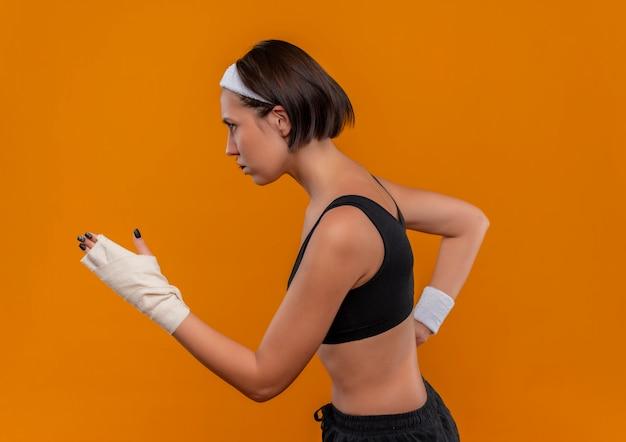 オレンジ色の壁を越えてトレーニングを実行しているヘッドバンドとスポーツウェアの若いフィットネス女性