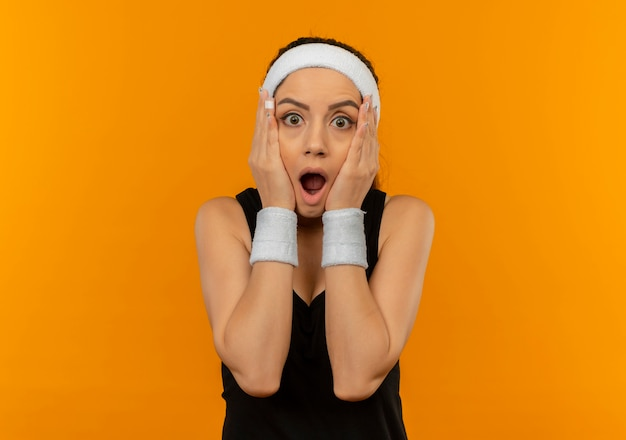 오렌지 벽 위에 서있는 그녀의 얼굴에 팔로 충격을받은 머리띠와 운동복에 젊은 피트 니스 여자